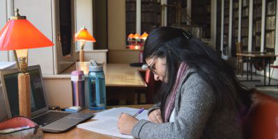 student working in the library with bookcase behind her